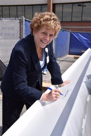 Kenda Aucker signing white beam at Topping out Ceremony